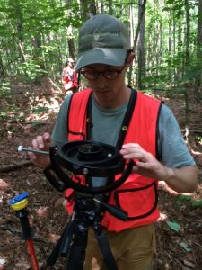 Environmental Science student uses a device in the woods